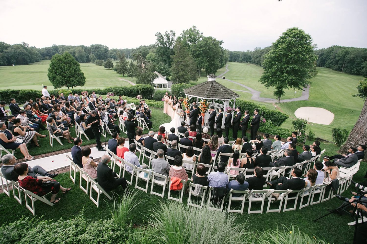 Wedding ceremony in a garden, country club-like setting along with plenty of greeneries