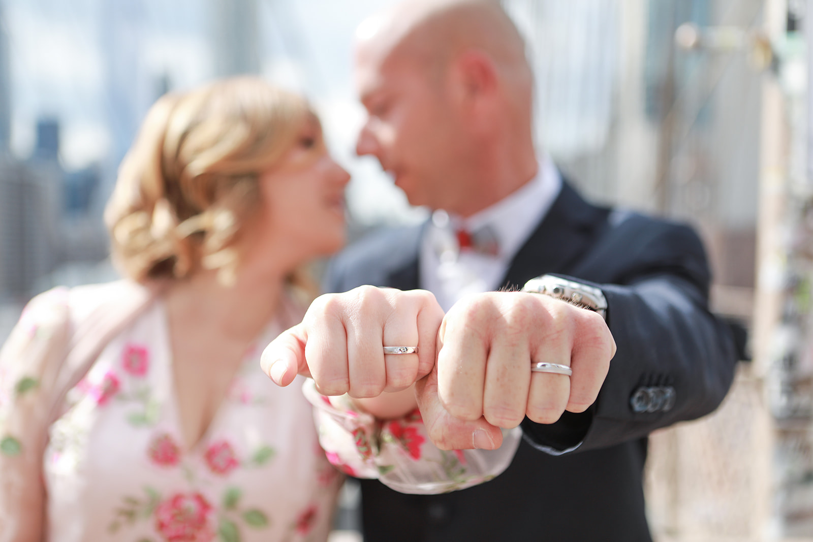 Couple posed for photo; holding out arms and showing fists with wedding rings on fingeres