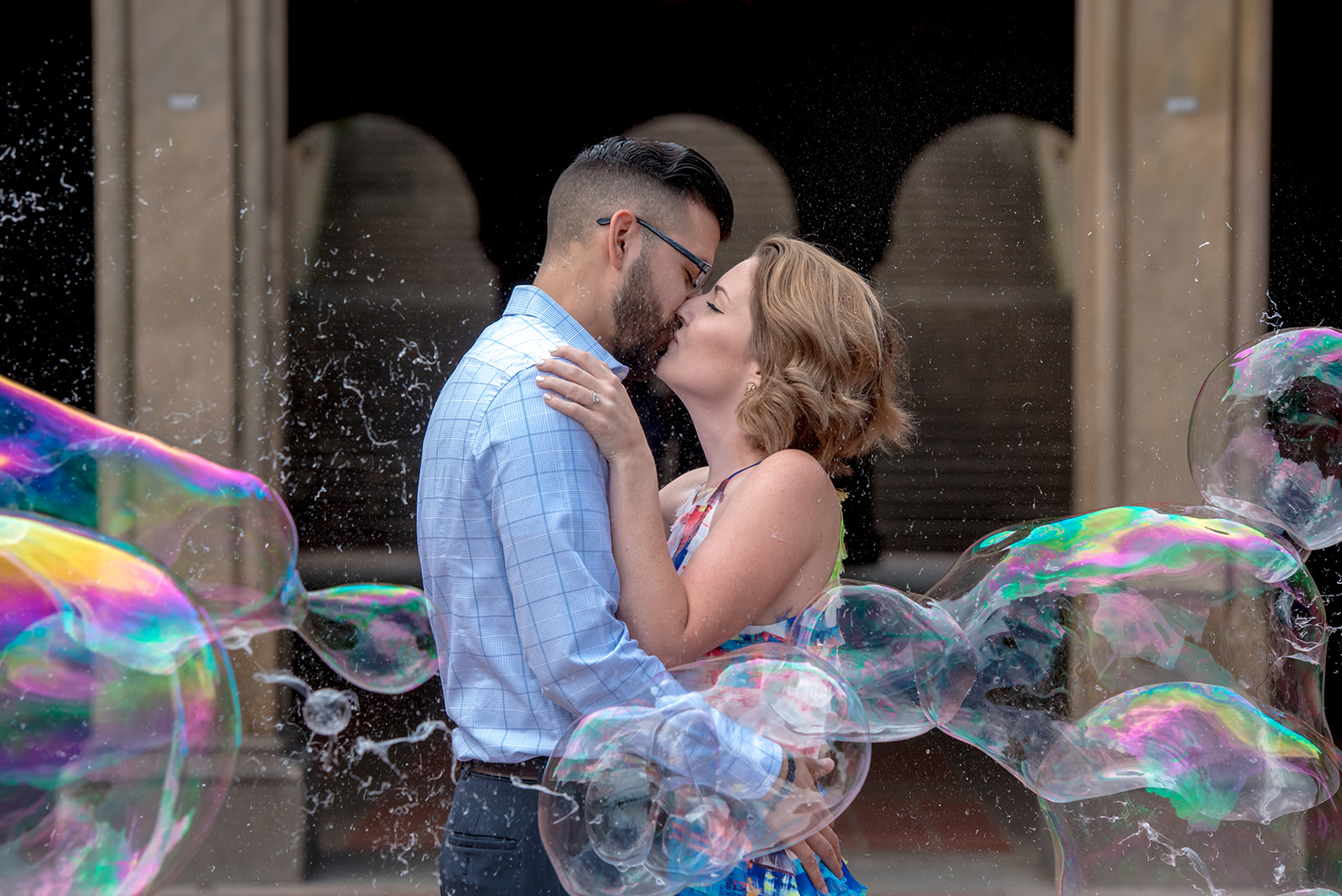 Couple kissing in Central Park with colorful bubbles surrounding them
