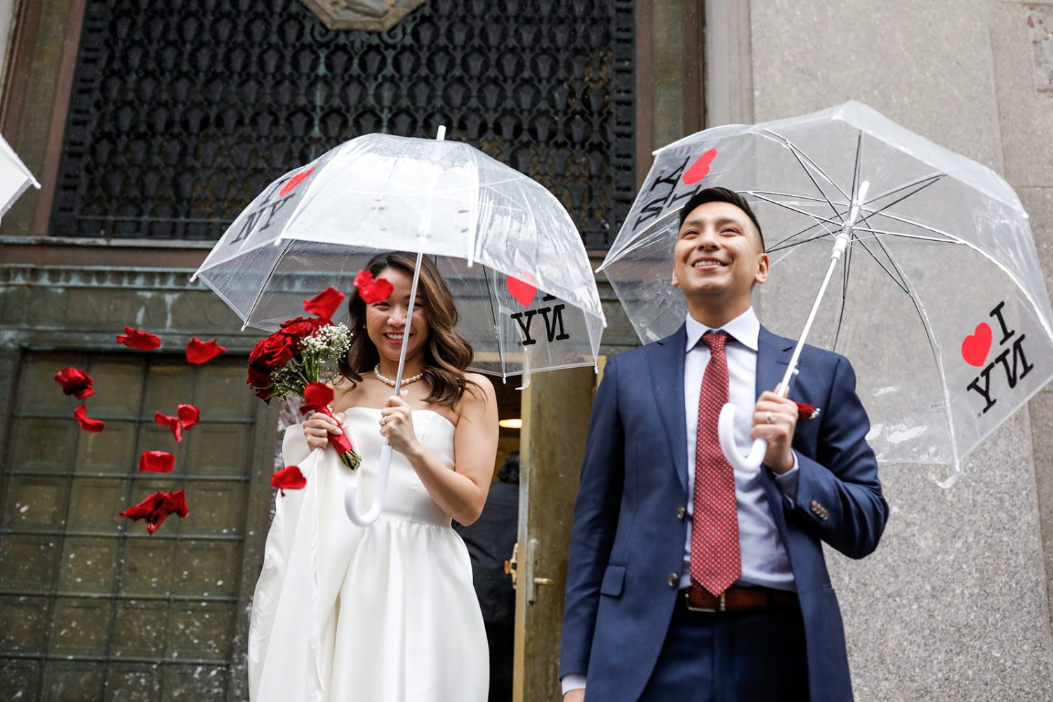 A couple got married walking out of NYC City Hall with raining rose petals