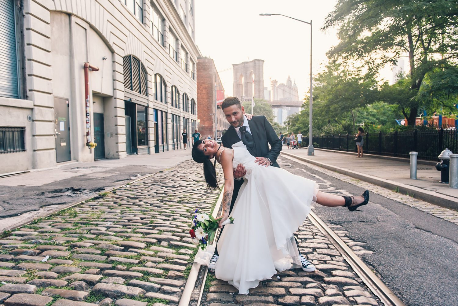 Couple posing for pre-wedding photoshoot on cobbled street in Dumbo